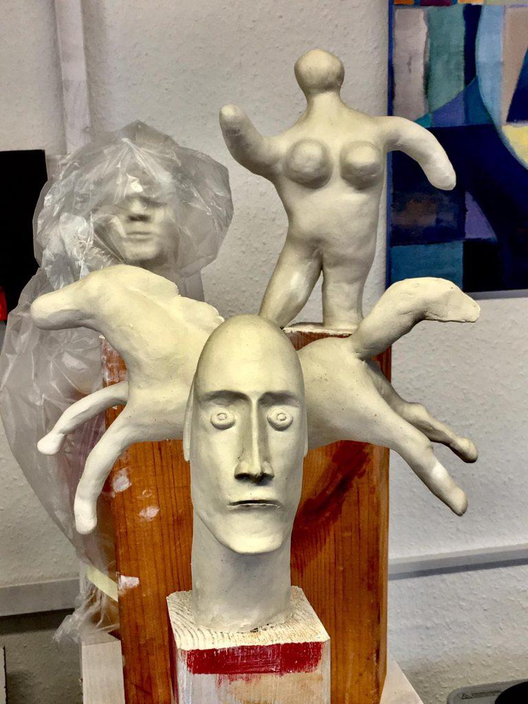das bild zeigt skulpturen eines männlichen Gesichtes, eines pferdes sowie eine weibliche figur.